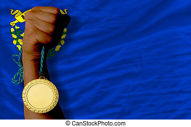 Winner holding gold medal for sport and flag of us state of nevada