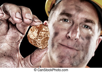 Gold miner with nugget - A gold miner shows a golden hugget...