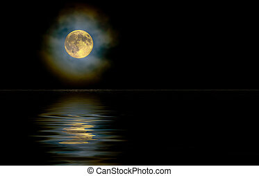 Gold moon through high clouds with reflection