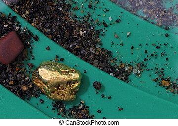 Natural Alaskan placer gold nugget in riffles of gold pan