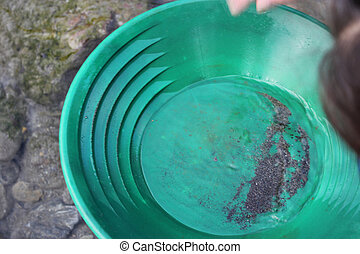Gold Nugget mining from the River, with a gold pan, cleaning...