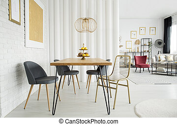 Gold open space interior - Gold lamp above dining table in...