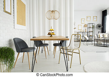 Gold open space interior - Gold lamp above wooden table and...