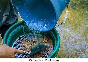 Gold panning and gem mining. Classifier used to sort and sift dirt, sand and pebbles to prepare to pan for gold and gemstones. Fun and adventure of prospecting.