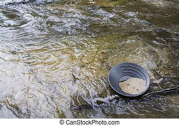 gold panning for gold - gold panning iin a small stream in...