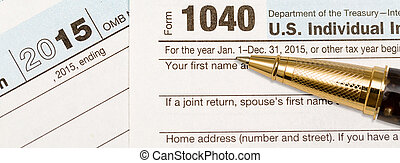 Gold pen laying on 2015 IRS form 1040 - USA IRS tax form...