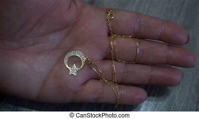 gold pendant in the form of a symbol of Turkey in a female hand
