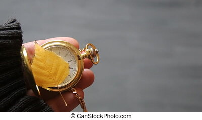 Gold pocket watch and autumn leaf
