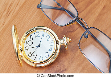 Gold pocket watch and glasses on a wooden background texture