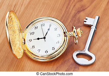 Gold pocket watch and key. Against the background of a wooden texture.