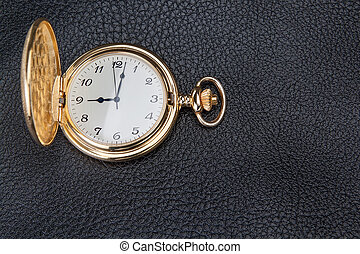 Gold pocket watch on a textured skin. Close-up.