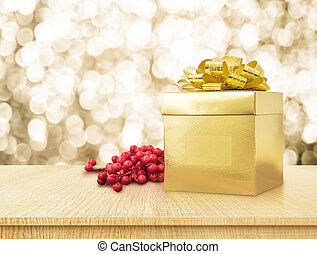 Gold present box and ribbon on wood table with sparkling gold bokeh light background, Holiday concept