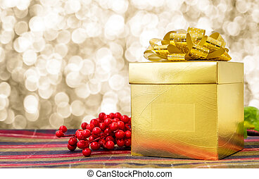 Gold present box with ribbon on table with sparkling gold bokeh light background, Leave space for adding your text