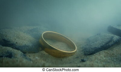 Gold Ring Drops Onto Rocks Underwater - Closeup shot of a...