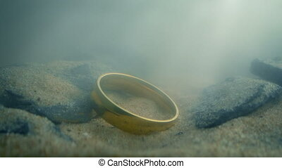 Gold Ring On River Bed - Gold ring deep underwater lit up in...