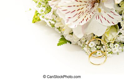 Gold rings for wedding bridal bouquet of flowers on