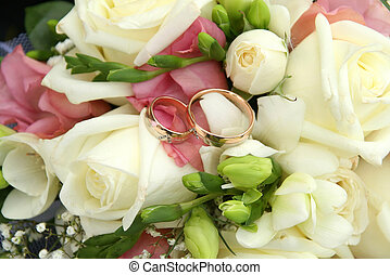 Gold rings on a bouquet of roses