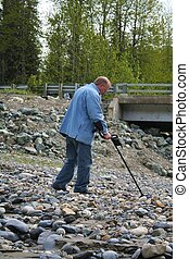 Gold Seeker - older man using a metal detector to search for...