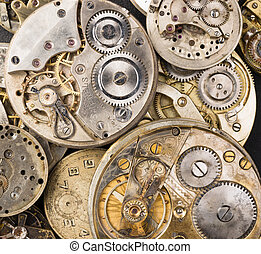 A pile of old pocket watches in various states
