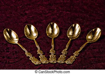 Gold spoons - Five gold spoons on purple velvet.