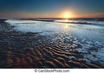 gold sunset over North sea sand beach at low tide