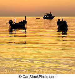 Gold sunset with longtail boats on tropical beach. Ko Tao island, Thailand