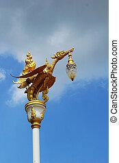 Gold swan bird on pole and sky