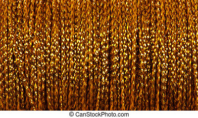 Coil with gold thread - abstract background. Macro photo.