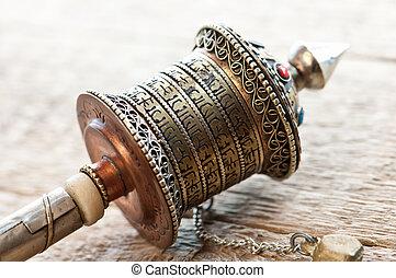 gold tibetan spool on table