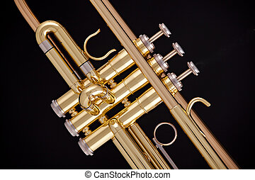 A professional gold trumpet isolated against a black background in the horizontal format.