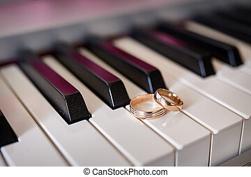 Gold wedding rings lie on the piano keys