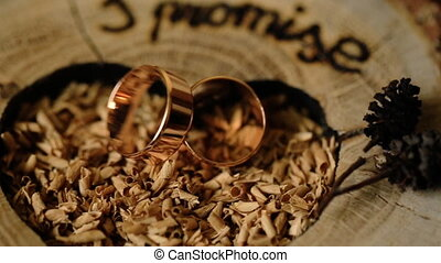 Gold wedding rings on a wooden background decorated for a marriage ceremony.