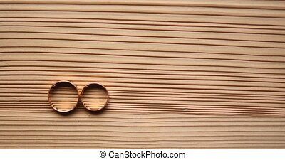gold wedding rings on a wooden background.