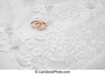 Gold wedding rings on white dress