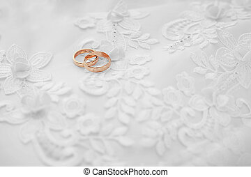 Gold wedding rings on white dress