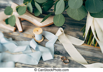 Gold wedding rings on with beige shoes of the bride and a spool with ribbon on a background of green leaves.