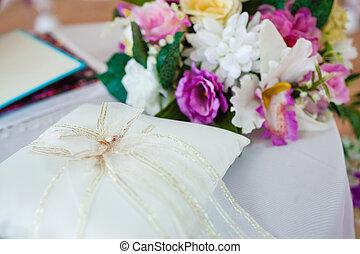 gold wedding rings on the pincushion