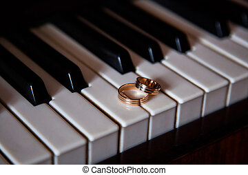 gold wedding rings, wedding bands on a black and white background, rings lie on the piano keys, rings in an unusual background