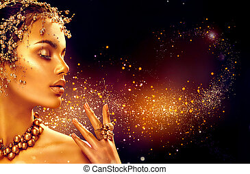 Gold woman skin. Beauty fashion model girl with golden makeup, hair and jewellery on black background