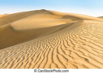 Gold yellow dunes under blue sky