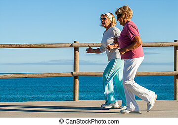 golden agers running at seafront. - Action portrait of...