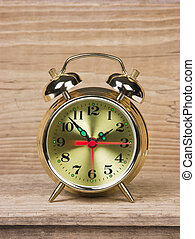 golden alarm clock on wooden table