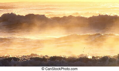 Telephoto shot of surf and spray glowing in golden late afternoon sun.