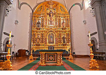 Golden altar and White Candles at Mission Basilica San Juan Capistrano Church California.  This is the successor church to the Mission founded by Father Junipero Serra in 1775.