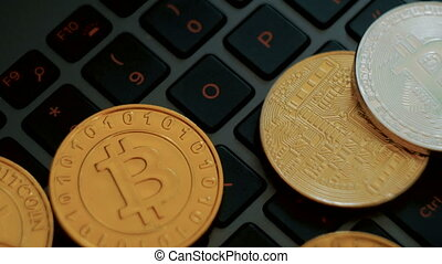 golden and silver bitcoins on keyboard, extreme close-up,...