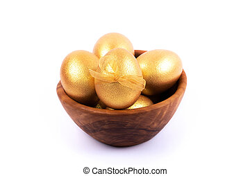 Golden and silver colored Easter eggs in wooden bowl isolated on white background. Place for text.