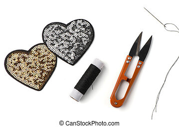 Golden and silver sequin heart patches, black thread, scissors and a needle