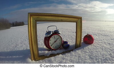 Golden art frame on field snow, Christmas bauble and clock,...