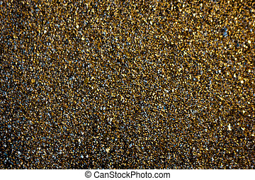 Golden background - dust of gold over black background.