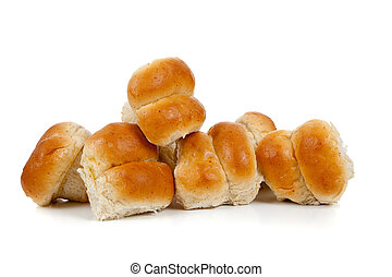 a Stack of golden baked dinner rolls on a white background